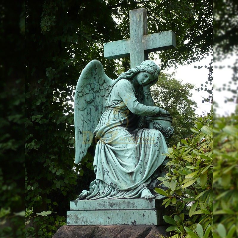 Female angel statue with cross used for outdoor grave decoration
